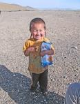 MONGOLIA 272 (HACIA UVURKHUSHUUT) …PERO NO LE BASTABA CON UNA Y A CONSEGUIDO EL PAQUETE (OBSERVAR LAS FINAS TRENZAS QUE LLEVA EL CRIO EN LA CABEZA)